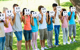 Friends holding smileys in front of faces. Group of multiethnic friends holding smileys in front of faces at park stock image