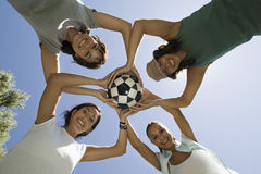 Friends Holding Soccer Ball Against Blue Sky Royalty Free Stock Photography