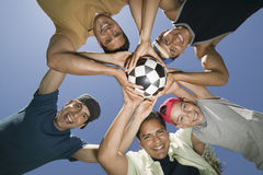 Friends Holding Soccer Ball Together In Huddle. Boy with friends and father holding soccer ball together in a huddle Royalty Free Stock Image