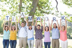 Friends holding teamwork signs in the park Royalty Free Stock Photo