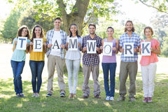 Friends holding teamwork signs in the park. On a sunny day Royalty Free Stock Photography