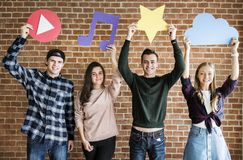 Friends holding up social media and technology concept icons Royalty Free Stock Photos