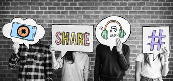 Friends holding up thought bubbles with social media concept icons royalty free stock photography