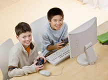 Friends holding video game controllers having fun Stock Photography