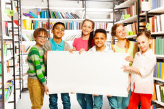 Friends holding white paper sheet in library Stock Photo