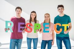 Friends holding word respect. Happy young friends holding colorful word respect and smiling at camera on grey Stock Image
