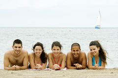 Friends in Holiday. Five friends are during a holiday posing to cam in front of the sea and a boat behind Stock Photos