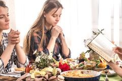 Friends at the holiday table praying before a meal. Home Holiday friends or family at the festive Easter table make a prayer before eating, the concept of stock photo