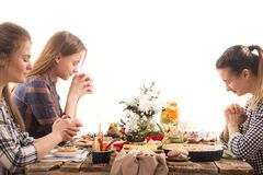 Friends at the holiday table praying before a meal. Home Holiday friends or family at the festive Easter table make a prayer before eating, the concept of stock photos