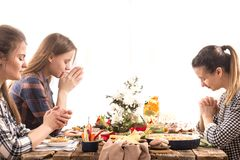 Friends at the holiday table praying before a meal. Home Holiday friends or family at the festive Easter table make a prayer before eating, the concept of royalty free stock photo