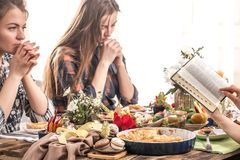 Friends at the holiday table praying before a meal. Home Holiday friends or family at the festive Easter table make a prayer before eating, the concept of stock photography
