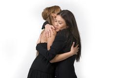 Friends Hugging. Two  cute  and young girls in black dress posing  over white background - hugging Royalty Free Stock Images