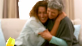 Friends hugging while sitting stock footage