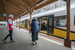 Friends hugging on the train station. Friends hugging before boarding ready to depart local train operated by Koleje Dolnoslaskie company standing on a platform Royalty Free Stock Photos