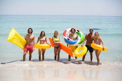 Friends with inflatable rings and pool rafts on seashore Royalty Free Stock Image
