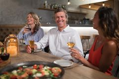Friends interacting while dining in restaurant. Happy friends interacting while dining in restaurant Stock Photo