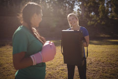 Friends interacting with each other while practicing boxing. In boot camp Stock Photography