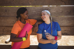 Friends interacting with each other after workout during obstacle course. In boot camp Royalty Free Stock Photography