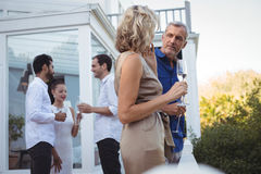 Friends interacting while having champagne in balcony Royalty Free Stock Images