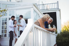 Friends interacting while having champagne in balcony Stock Photos
