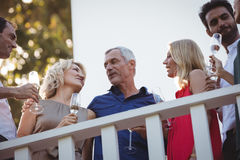 Friends interacting while having champagne in balcony Royalty Free Stock Image