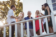 Friends interacting while having champagne in balcony Royalty Free Stock Photo