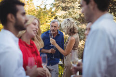 Friends interacting while having champagne in balcony Stock Photo