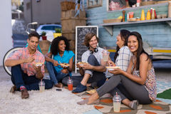 Friends interacting while having snacks and juice. Happy friends interacting while having snacks and juice Stock Photos