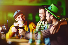 Friends in Irish Bar. Three slightly drunk friends dressed in traditional green enjoying dark beer during meeting in Irish Pub on St. Patricks day Stock Photography