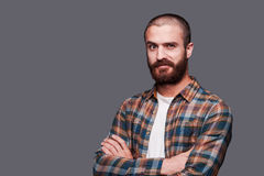 In friends with irony. Handsome young bearded man keeping arms crossed and expressing ironic smile while standing against grey background Stock Photos
