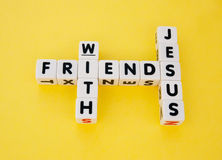 Friends with Jesus. Text ' friends ', ' with ' and ' Jesus ' inscribed on small white cubes in uppercase letters and arranged crossword style with common letters Royalty Free Stock Image
