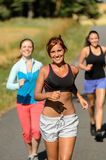 Friends jogging together outdoors sunny path Stock Photos