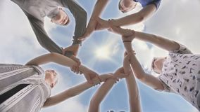 Friends join their hands in a circle. The concept of strong friendship. stock video