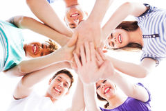 Friends joining hands. Young friends standing in huddle Royalty Free Stock Image