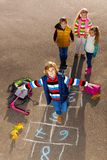 Friends jump on drawed hopscotch. Boy jumping on hopscotch game with friends boys an girls standing by with school bags laying near Royalty Free Stock Images