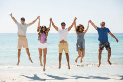 Friends jumping with arms raised at beach Stock Image