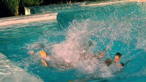 Friends jumping back into swimming pool together stock video