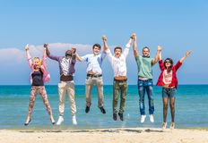 Friends jumping on the beach Stock Photos