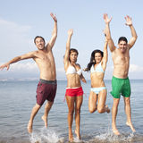 Friends jumping on the beach with hand up Stock Images