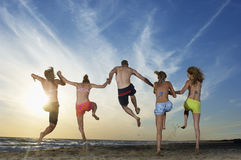 Friends Jumping On Sand While Holding Hands At Beach Stock Photo