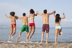 Friends jumping into the sea Stock Photo
