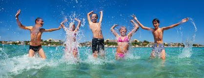Friends jumping and splashing at shallow water royalty free stock image