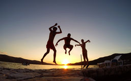 Friends jumping at sunset on the beach Royalty Free Stock Photo