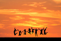 Friends jumping in sunset Royalty Free Stock Photos