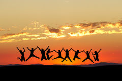 Friends jumping in sunset sky Royalty Free Stock Photos