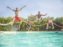Friends jumping in a swimming pool Stock Images