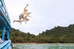Friends jumping to the sea from boat, having fun together, beach tropical vacation stock photos