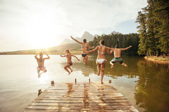 Friends jumping into the water from a jetty. Portrait of young friends jumping into the water from a jetty. Young people having fun at the lake on a summer day Stock Photos