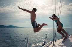 Friends jumping into water from a sailing boat Stock Photos