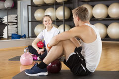 Friends With Kettlebells On Exercise Mat In Gymnasium Royalty Free Stock Images